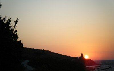 Puesta de sol en el estrecho con torre almenara